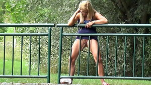 Pretty Blonde Urinates Through Railings